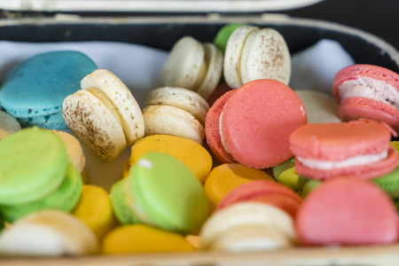 Close-up of colourful French macarons randomly placed in a box