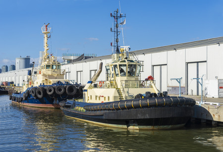 berth: View of two tugboats berthing in a dock during daytime