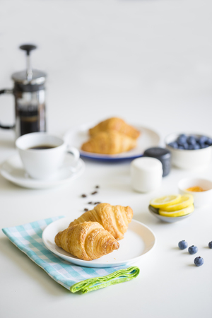 Croissants, cup of coffee, blueberries, lemon slices on table Stock Photo - 63697121