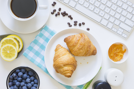 Overhead shot of breakfast including croissants, blueberries, a cup of coffee and coffee beans, on table with keyboard Stock Photo - 63697125