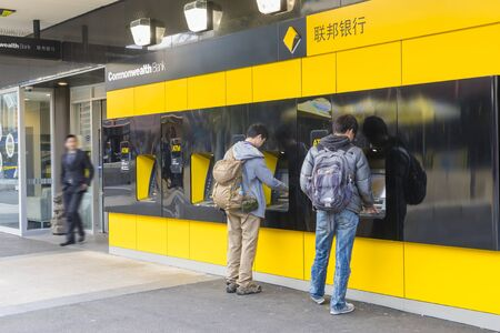 Melbourne, Australia - September 4, 2015: View of two persons using the ATMs outside the Commonwealth Bank in Melbourne while a man walking out of the bank.