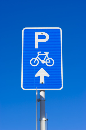 Bicycle parking sign showing parking spaces ahead for bicycles against the blue sky Stock Photo - 64018188