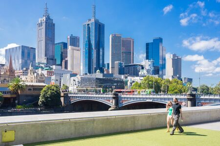 Melbourne, Australia - February 27, 2016: Tourists walking with Melbourne skyline as the background during daytime. Melbourne is ranked the worlds most liveable city in sixth consecutive years.