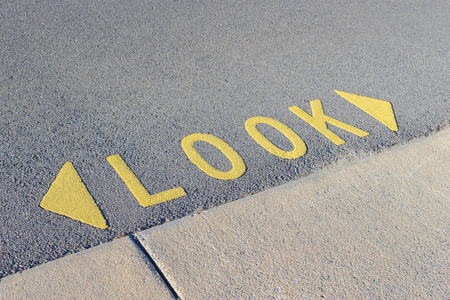 Look wordings and arrows in yellow on the road Stock Photo
