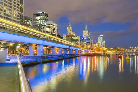 Melbourne, Australia - September 18, 2015: Multiple exposure image of skyscrapers and light trail of trains in downtown Melbourne, Australia at twilight. Stock Photo - 61817458