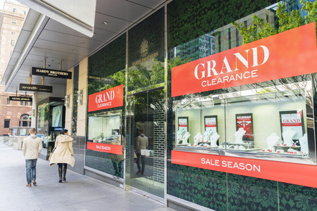 shopfront: Sydney, Australia - June 26, 2016: People walking pass Hardy Brothers Jewellery store in downtown Sydney with grand clearance signs in the shopfront.