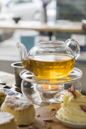 Afternoon tea with glass teapot with tea, scones and cream on table in a cafe