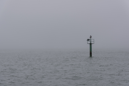 Marker post in a sea with misty background at Portsmouth, England, United Kingdom