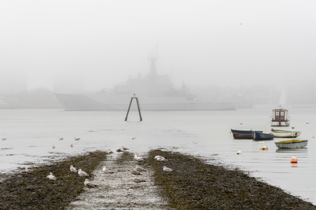 Naval ship passing in the foggy sea in Portsmouth