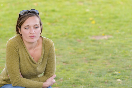A sad and depressed woman sitting on the grass deepley in thoughts