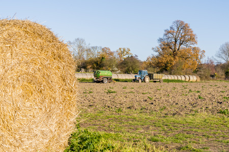A view of farm machinery behind the bale of straw Stock Photo