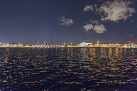 Night shot of Neva River and St Petersburg landmarks of split of the Vasilievsky Island - Rostral Columns and the Stock Exchange building in St Petersburg, Russia
