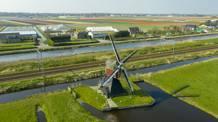 Aerial view of a old dutch traditional windmill on the rural countryside in The Netherlands with a dike, canals. railway. bridge and a road.