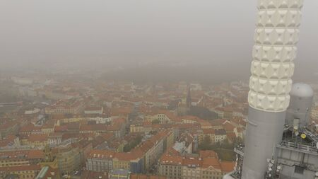 Aerial view of citycape of old town of Prague, with a lot of rooftops, churches, and the landmark of Tower Park Praha. View from a Mavic drone.