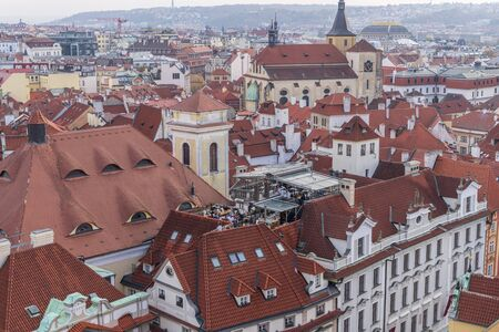 Aerial view of citycape of old town of Prague, with a lot of red rooftops and churches