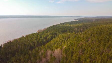Aerial view of the Vuoksi river, the forest and the settlement in autumn day, Losevo, Leningrad Oblast, Russia