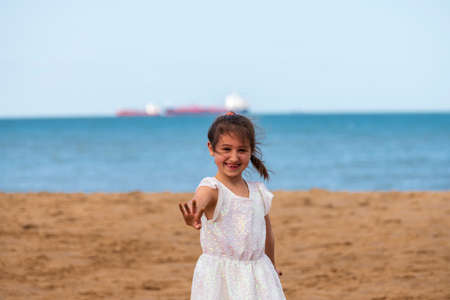 Adorable young girl posing at the beach in white dress, Botany Bay, Kent, UK