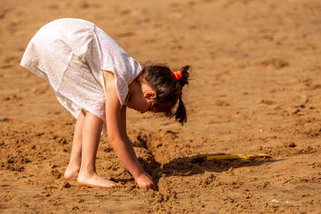 Happy child playing with sand at the beach in summer, Botany Bay, Kent, UK