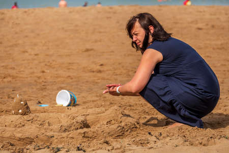 Sad woman playing with sand at the beach in summer, Botany Bay, Kent, UK
