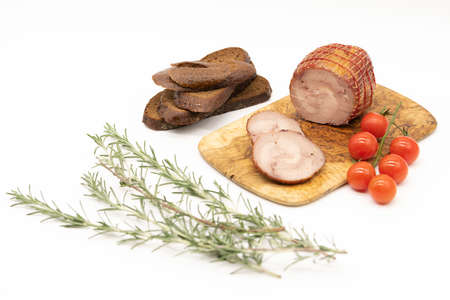 Smoked Turkey roll with herbs on a wooden background.