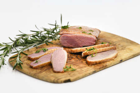 Smoked duck sliced with herbs on a wooden background.