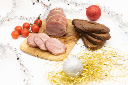 Baked Turkey roll with tomatoes and brown bread on a Christmas wooden background