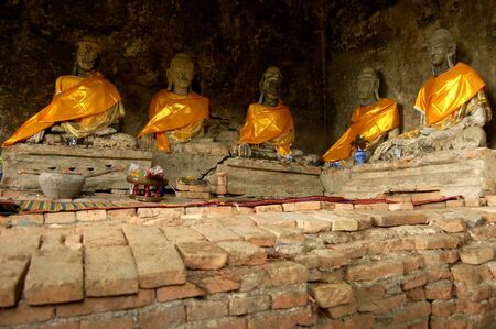 Buddhism take a monk cloth wear on an old Buddha image in ruin temple photo