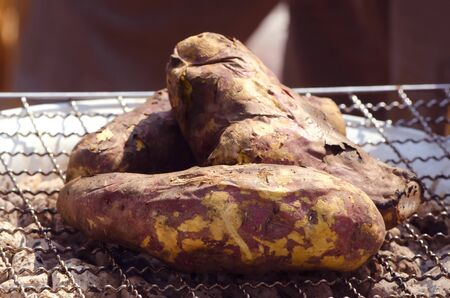 yam: A sweet potato on a gridiron grill by charcoal with the sunlight in a organic food market