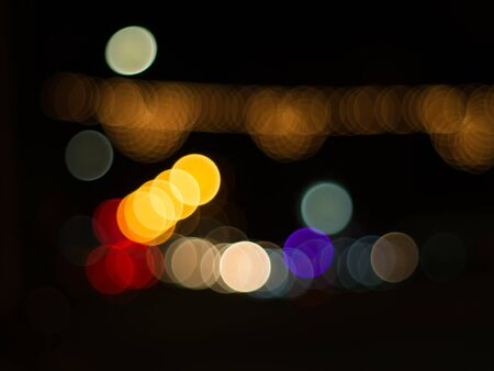 Blurred lights at night time on road in center city. Background and circle  bokeh for christmas and New year festival.