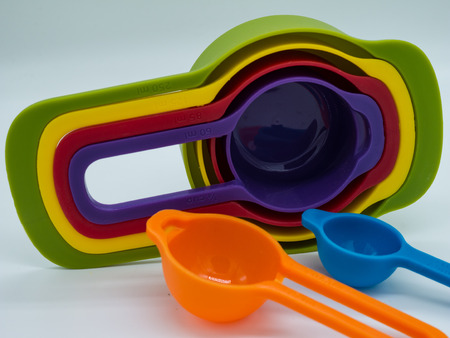 collapsible: Colorful plastic measuring cups set and measuring cups different sizes on white background.