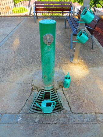 Green drinking park fountain with set of four green plastic watering cans and wooden benches bottom for sitting