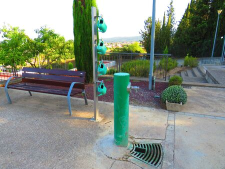 Green drinking park fountain with set of four green plastic watering cans and wood bench bottom for sitting Stock fotó