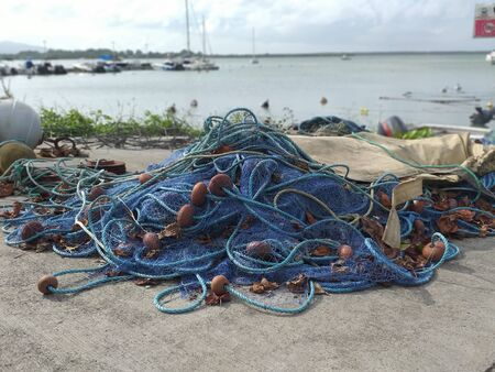 Set of blue fishing nets and ropes of different sizes on a pier in the fishing port of the Caribbean town. Turquoise and calm waters. Blue sky with small white clouds.