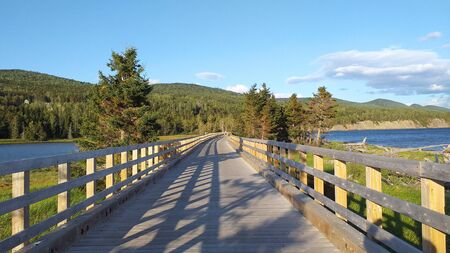 Wooden bridge marking the path and mountains with vegetation of the Forill?n National Park. Greenish, blue and yellow hues .--- Forillon, one of 42 national parks and park reserves, located near Gasp?, eastern Quebec. Stockfoto - 133474262
