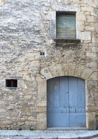 Light blue wooden door in a stone facade. Small window Elegant entrance Rustic