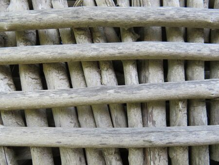 Background Window enclosure made of wood logs without bark. Martinique, French West Indies. Caribbean Stockfoto - 133474413
