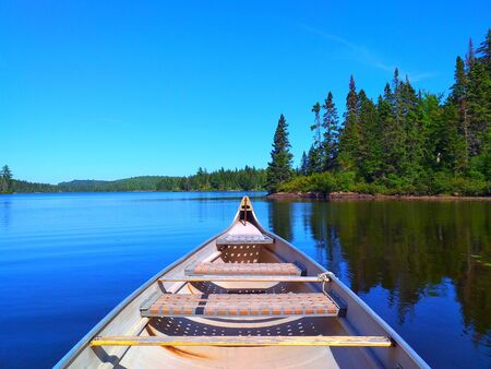 A canoe resting by the calm water in beautiful lake. La Mauricie National Park, Quebec Canada.Look out point with blue sky and tranquil waters landscape Stock Photo