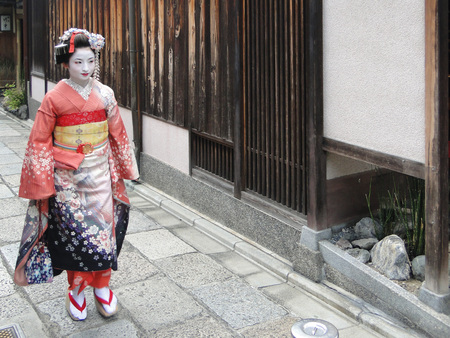Kyoto, Japan, September 12, 2014: Maiko geisha walking on a street of Gion in Kyoto Japan. Traditional Japanese Kimono And Okobo - Tall Wooden Shoes