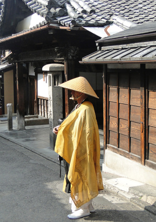 Kyoto, Japan - September 18, 2014: Japanese Shintoist monk in traditional yellow dress in Kyoto street. Editorial