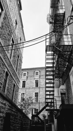 Fire stairs in the back of stone house buildings in the old town of Quebec City, Canada. Black and white photo of fire escape in stone buildings of old Quebec. Industrial architecture Urban style Reklamní fotografie