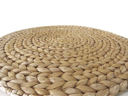 top view texture of handmade round beige wicker tablecloth surface isolated on white background; Close-up of single oval water mat of water hyacinth fabric. Rustic appearance Heat-resistant. Environmentally friendly.