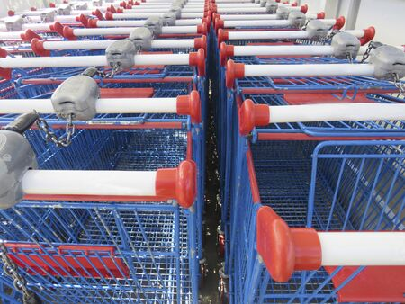Rows of blue shopping carts collected in supermarket. Double lined shopping carts.