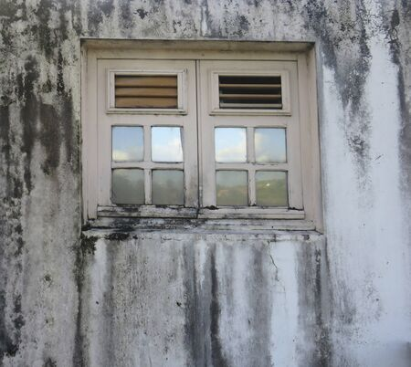 Closeup of rusty wooden window on white and black wall. Traditional architecture of the Antilles. Martinique, French West Indies