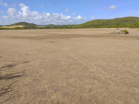 Panoramic photo of dry salt pans of ocher color. Blue sky with tropical clouds and mountains with vegetation. Martinique, French West Indies. Stockfoto