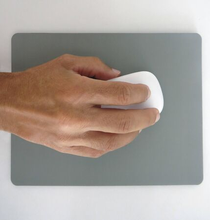 mans hand holding a white computer mouse and gray mouse pad