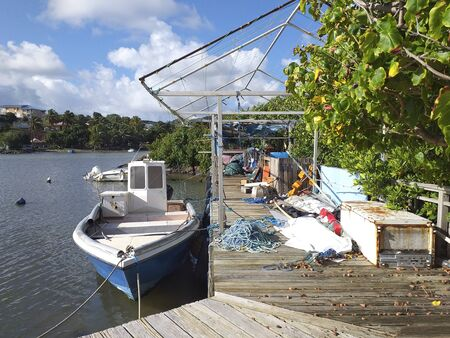 Caribbean pier with fishing boat moored. Tropical landscape. Blue sky with white tropical clouds. Stockfoto