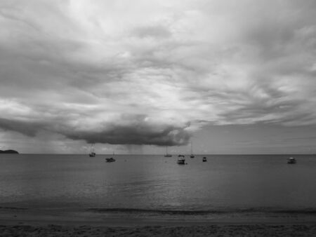 Black and white image of the Caribbean Sea with silhouette of boats and tropical storm clouds