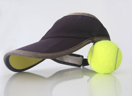 Isolated tennis ball with black visor on white background.