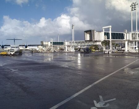 Airport fingers on wet runway, plane and service vehicles in Caribbean storm sky. Travel and industry concepts