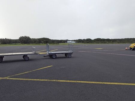 Empty luggage cart on the runway of the airport